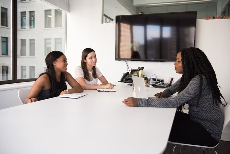 woman being interviewed by two other women in an office