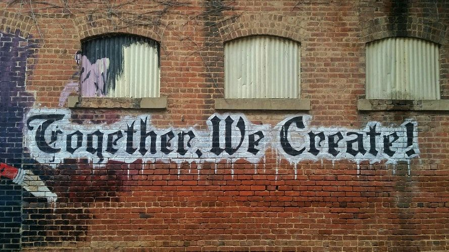 graffiti painted on a wall saying 'together we create'