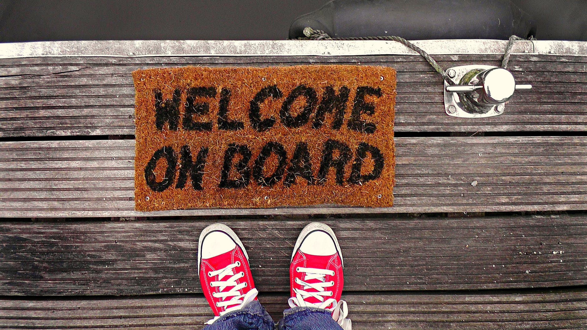 doormat saying welcome onboard on a dock next to a pair of feet