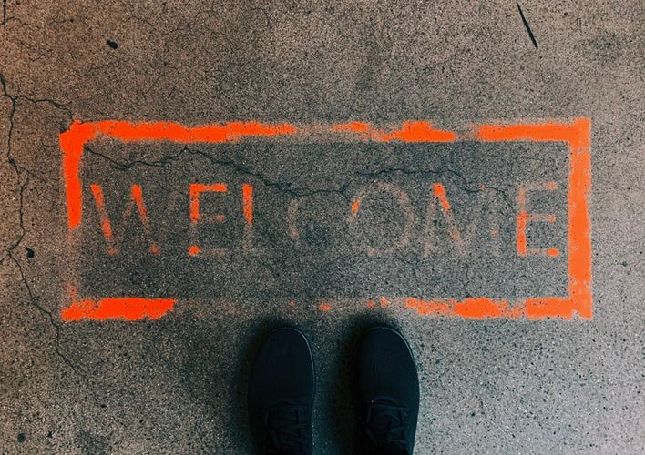 feet standing in front of the word Welcome stenciled in orange paint on the ground