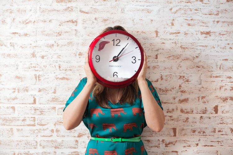 woman standing against a exposed brick wall and holding a large clock in front of her face