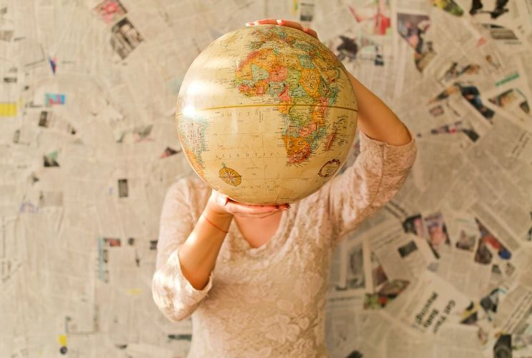 woman holding a globe in front of her face