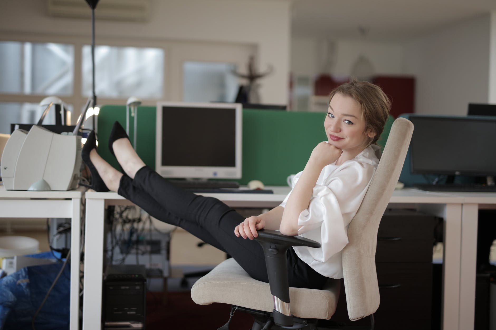 woman in office chair with her feet on the desk looking relaxed