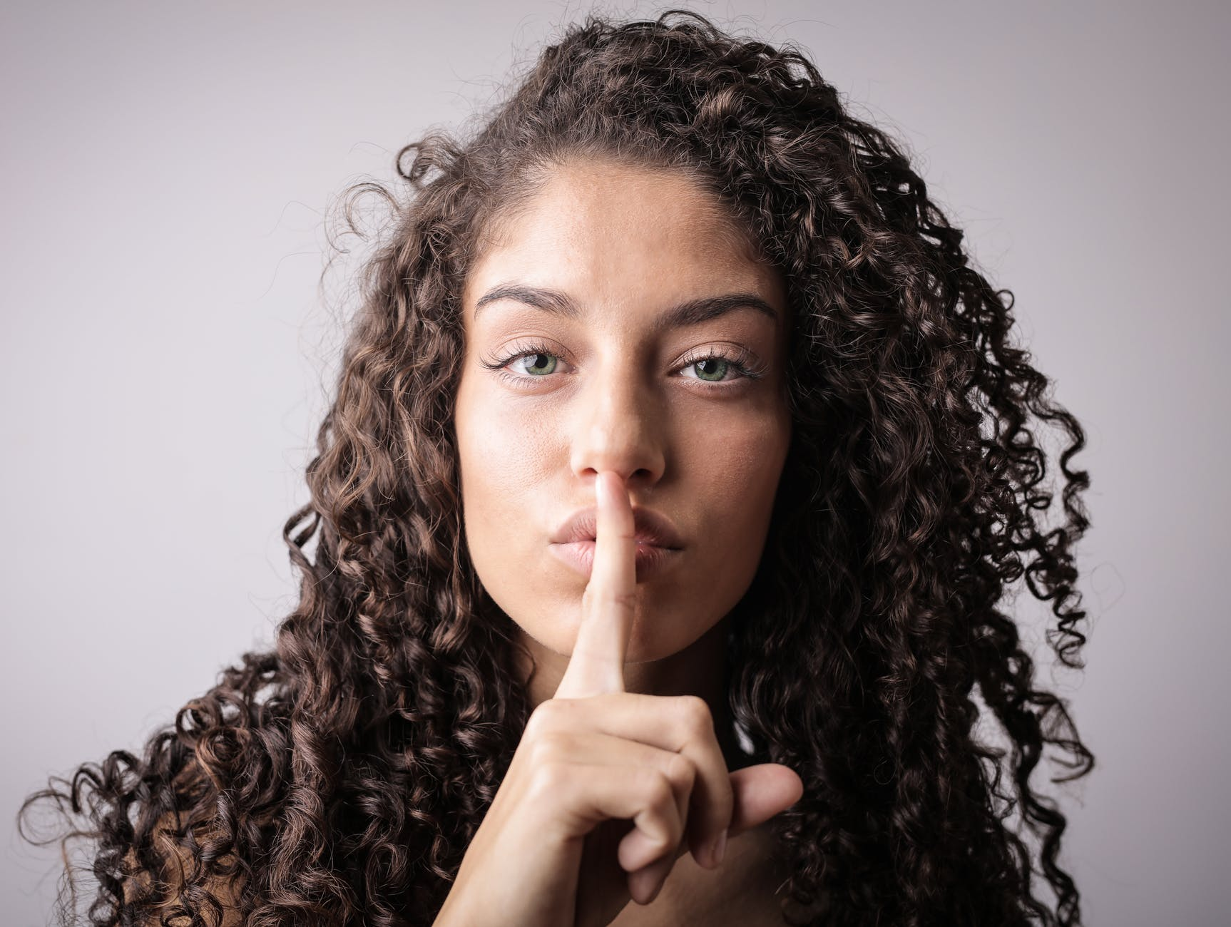 woman holding her finger to her lips as if to say 'shhh'
