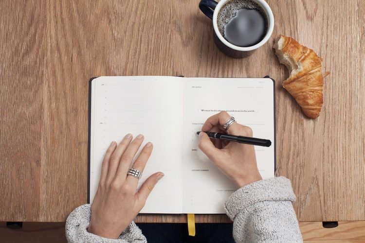 woman at a desk writing a list in a notebook