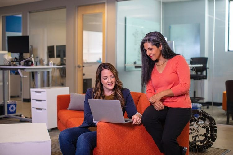 two women sitting on an office sofa with one showing the other something on a laptop