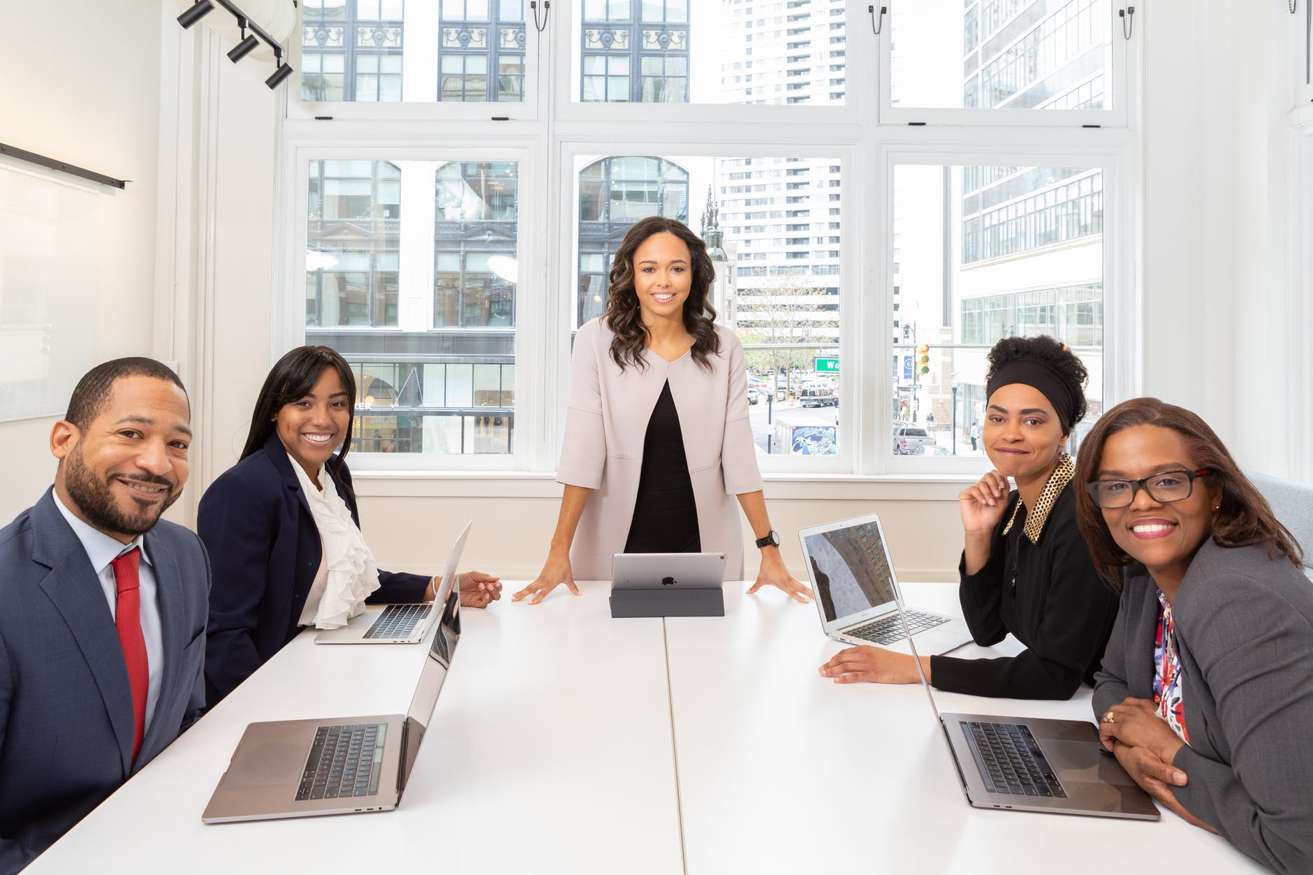 boss at the head of a conference room table with her smiling team