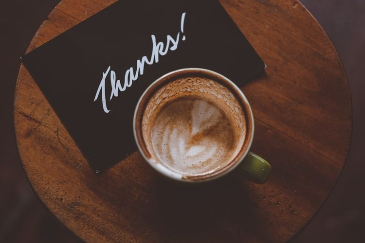 a cup of coffee and a note saying thanks