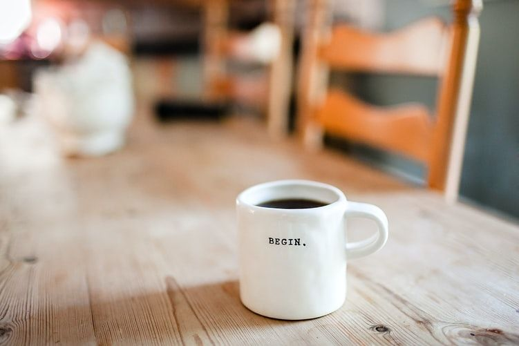a coffee mug with the word 'begin' printed on it sitting on a table