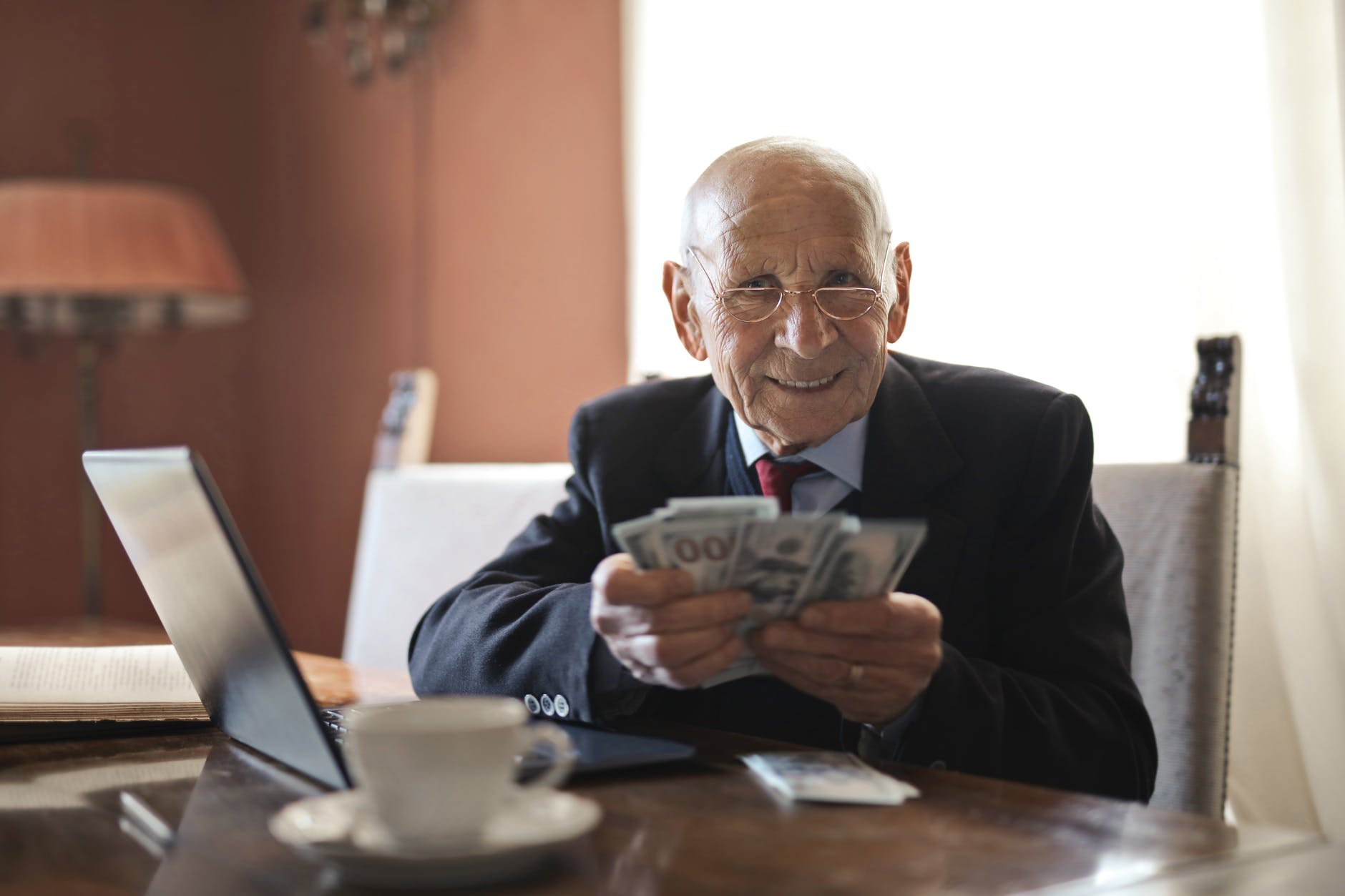 elderly businessman sitting in front of laptop holding a fan of manner