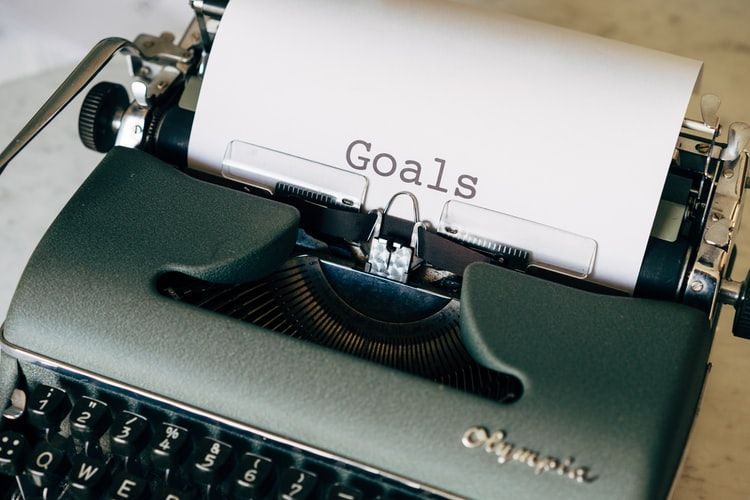 the word 'goals' typed on a piece of paper coming out of an old fashioned typewriter
