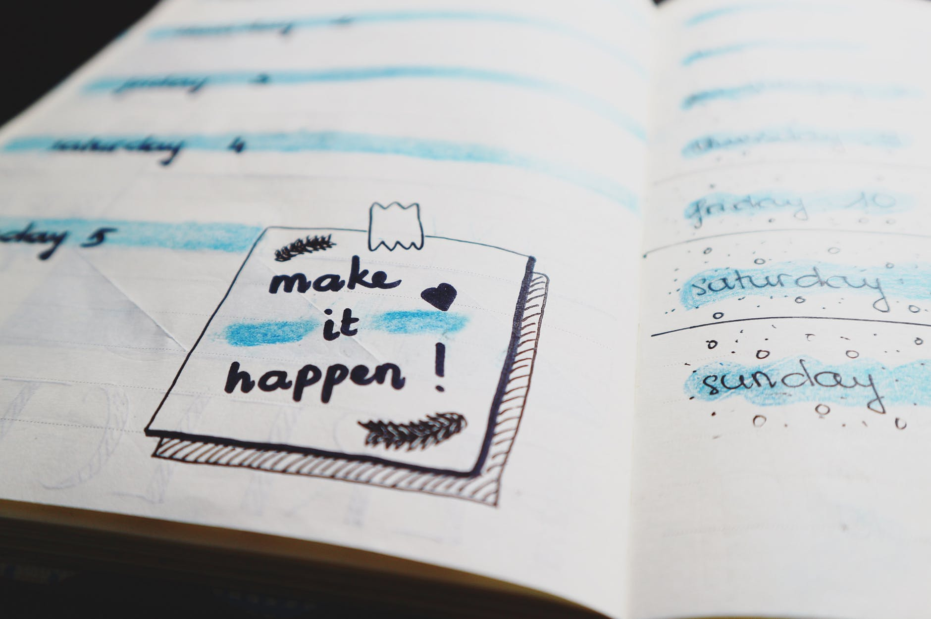 the words 'make it happen' doodled in a notebook