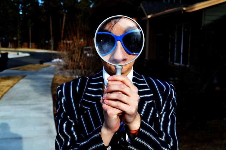 man in pin striped blazer holding a magnifying glass up in front of his face