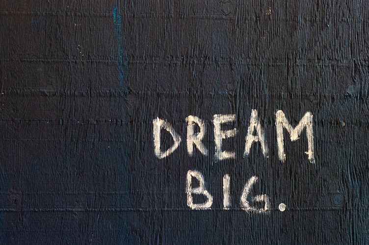 the words 'dream big' painted on a black background