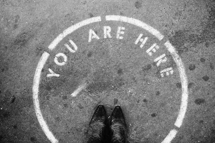 pair of feet standing in a circle painted on the ground with the words 'you are here'
