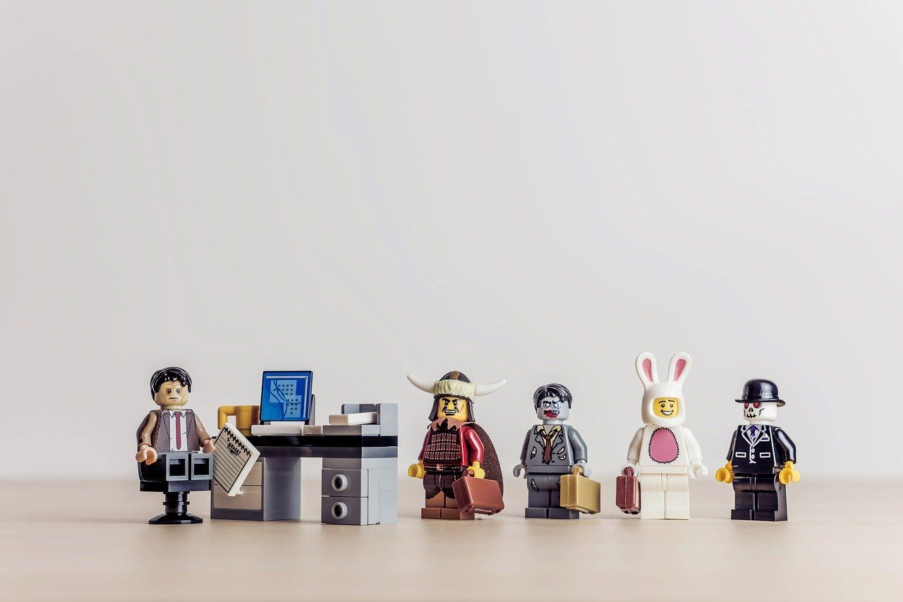 Lego figures lining up at a desk for a job interview