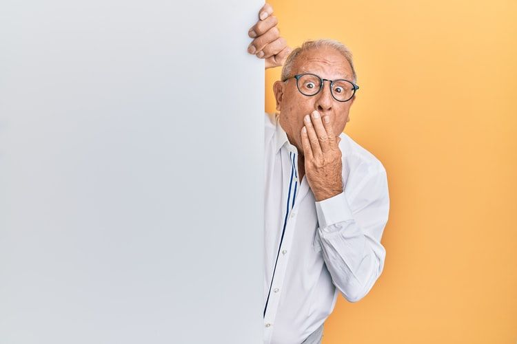 man peeking around a corner with his hand over his mouth as if to say 'oops'