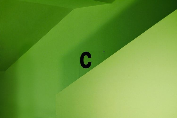 the letter C painted in black on a lime green wall