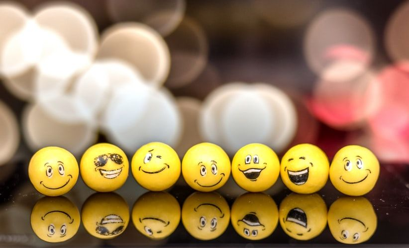 yellow ping pong balls with emoji faces on them